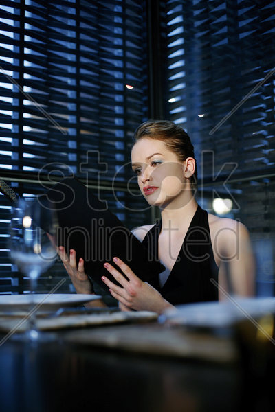 woman reading menu in a restaurant stock photo