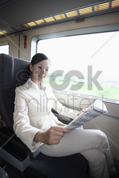woman reading newspaper while traveling on the train stock photo
