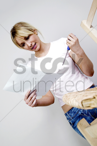 woman reading the instruction on how to fix a chair stock photo
