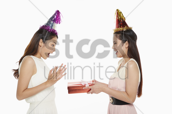woman receiving a gift from a friend stock photo
