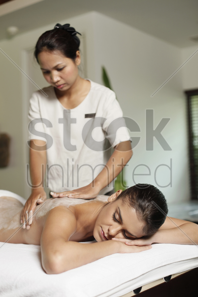 woman receiving back massage with coconut scrub stock photo