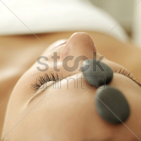 woman receiving hot stone treatment stock photo