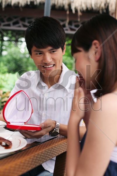 woman receiving present from her boyfriend stock photo