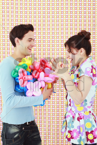 woman receiving sculpted balloons from man stock photo