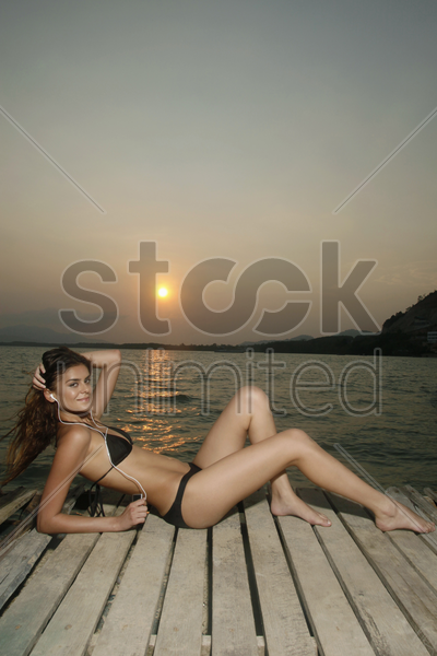 woman relaxing and listening to music on the pier stock photo