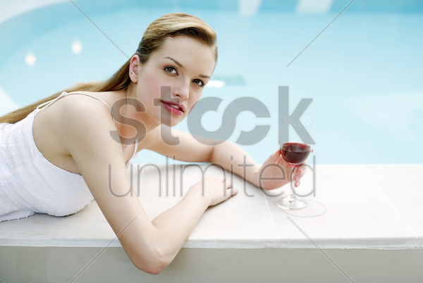 woman relaxing by the pool side drinking red wine stock photo
