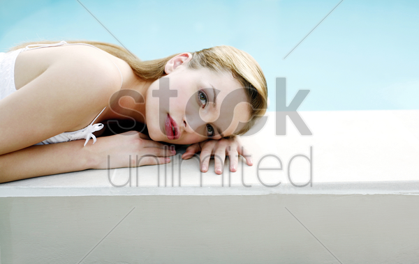 woman relaxing by the pool side stock photo