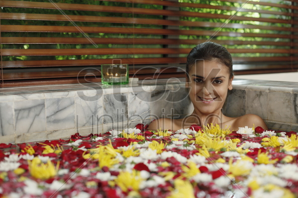 woman relaxing in bathtub with flower petals stock photo