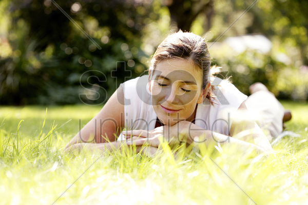 woman relaxing in the park stock photo