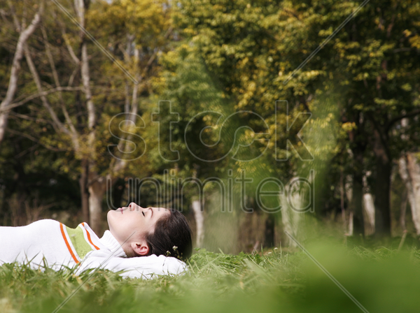 woman relaxing on the grass stock photo