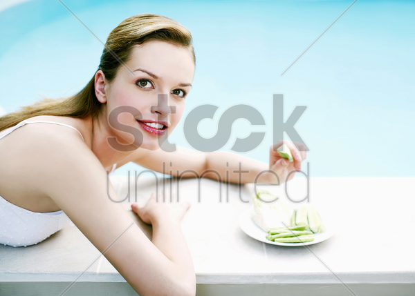 woman resting by the pool side eating green vegetables stock photo