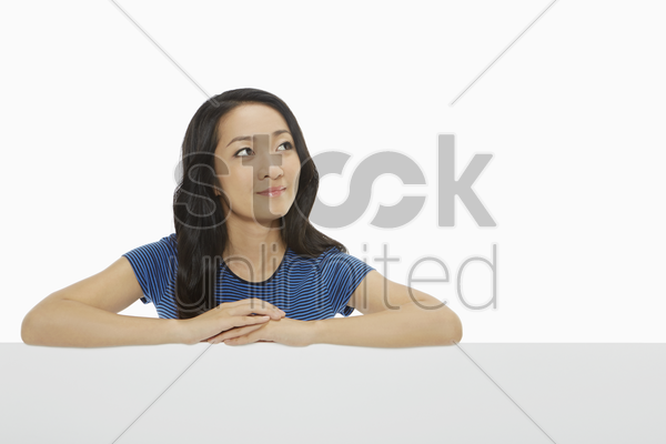woman resting her arms on a wall stock photo