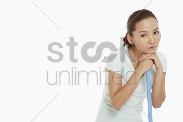 woman resting her chin on a mop stock photo