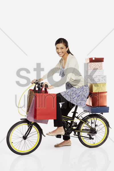woman riding a bicycle, carrying gift boxes and shopping bags stock photo