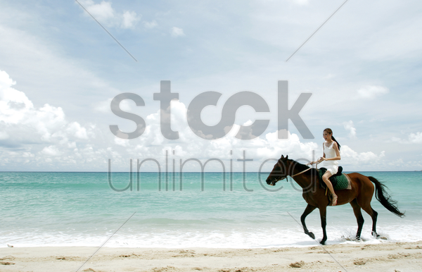 woman riding a horse on the beach stock photo