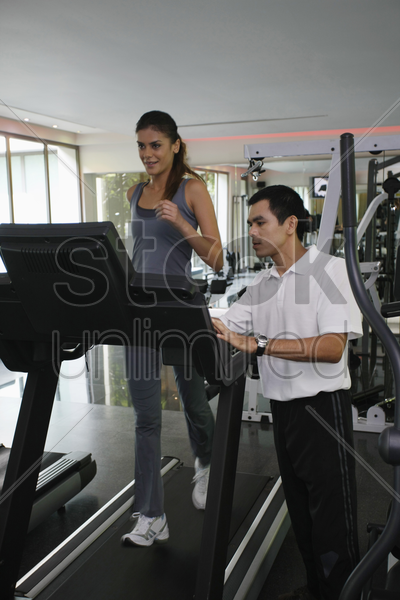 woman running on treadmill, personal trainer watching stock photo