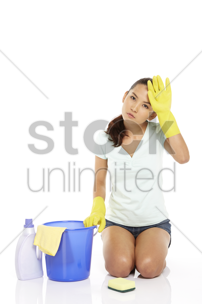 woman scrubbing the floor, feeling exhausted stock photo
