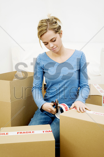 woman sealing up boxes stock photo