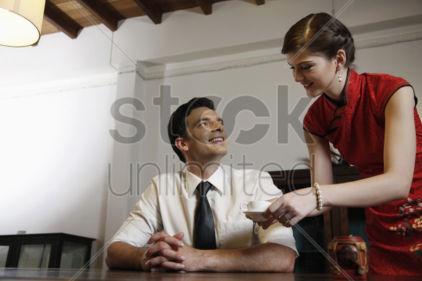 woman serving businessman with a cup of tea stock photo
