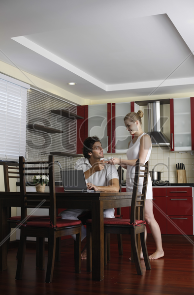 woman serving man a cup of coffee, man using laptop stock photo