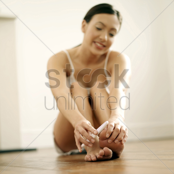 woman shaping her toe nails stock photo