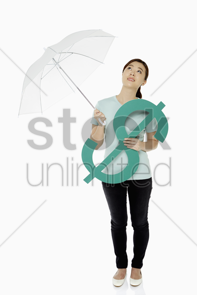 woman shielding the dollar sign with an umbrella stock photo