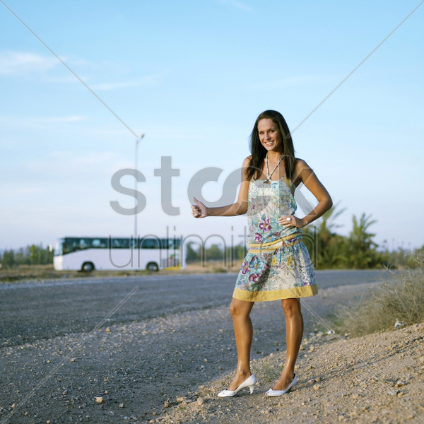 woman showing a hitch hiking gesture stock photo