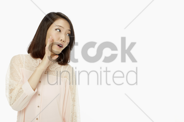 woman showing a whispering hand gesture stock photo