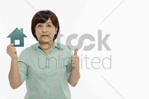 woman showing hand gesture while holding a cut out house stock photo