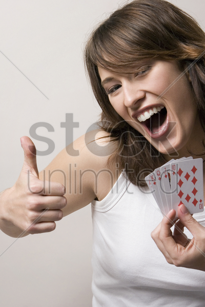 woman showing thumbs up while holding playing cards stock photo