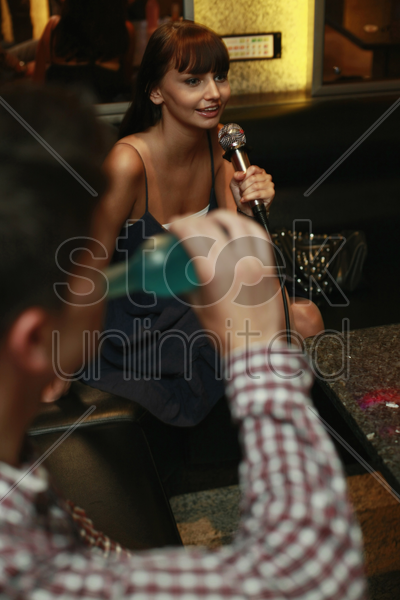woman singing into microphone, man drinking stock photo