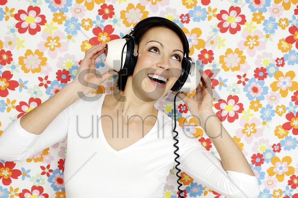 woman singing while listening to music on the headphones stock photo
