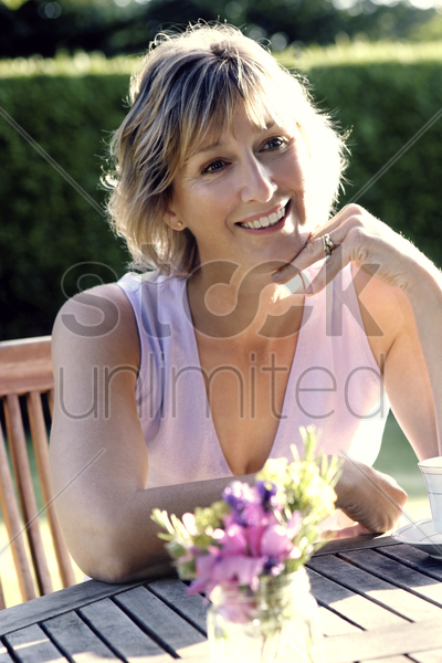 woman sitting alone smiling stock photo