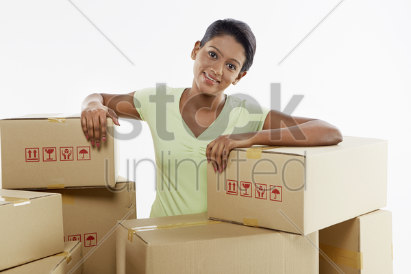 woman sitting amongst cardboard boxes stock photo