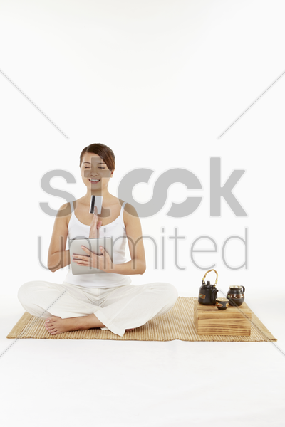 woman sitting and meditating with digital tablet and credit card stock photo