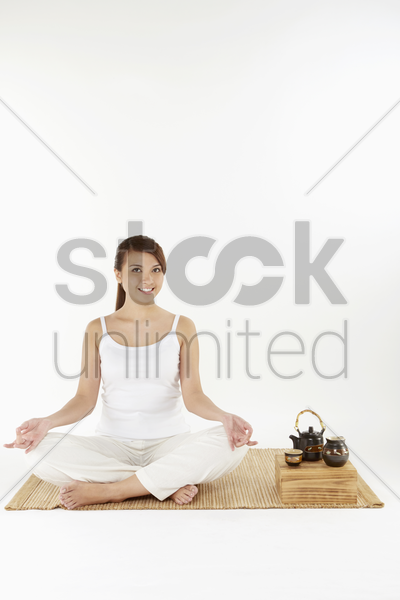 woman sitting and meditating stock photo