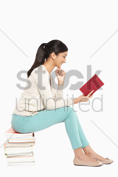 woman sitting and reading a book stock photo
