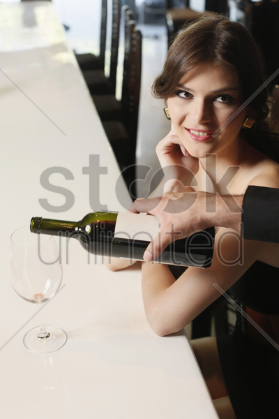 woman sitting at the bar, wine being poured into her glass stock photo