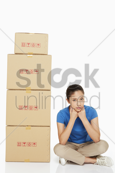 woman sitting beside a stack of cardboard boxes stock photo