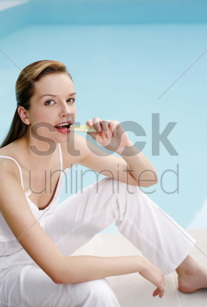 woman sitting by the pool side eating cucumber stock photo