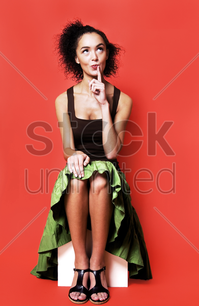 woman sitting down and thinking stock photo