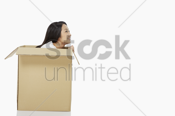 woman sitting inside of a cardboard box, smiling stock photo