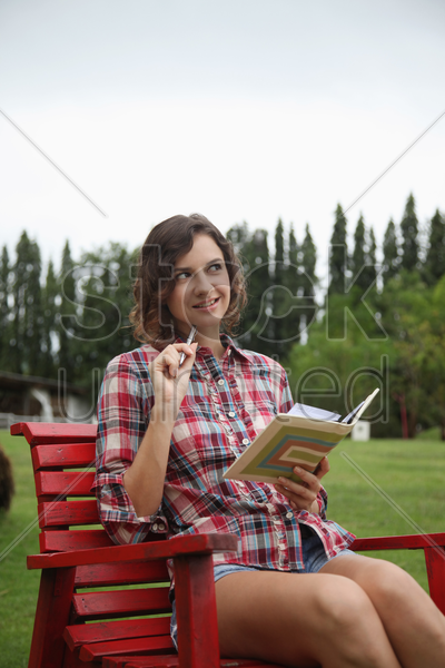 woman sitting on a chair, writing diary stock photo