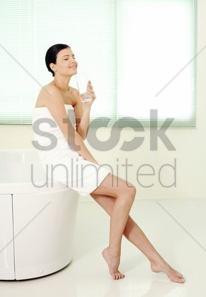 woman sitting on bathtub ledge holding a glass of water stock photo