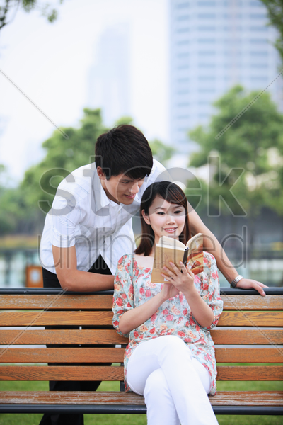 woman sitting on bench reading book, man watching from behind stock photo