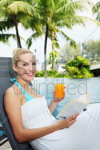 woman sitting on lounge chair by the pool reading a book stock photo