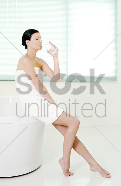 woman sitting on the bathtub corner drinking a glass of water stock photo