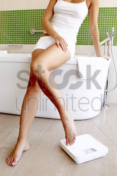woman sitting on the bathtub stock photo