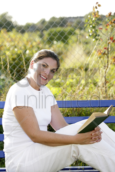 woman sitting on the bench reading book stock photo