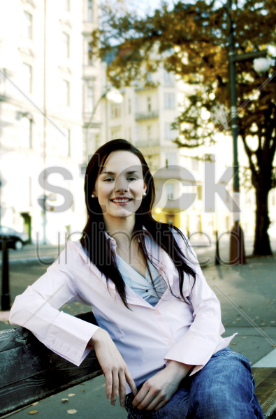 woman sitting on the bench smiling stock photo